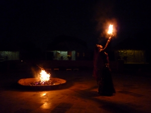 Traditional folk dancer spiting fire in the desert camp